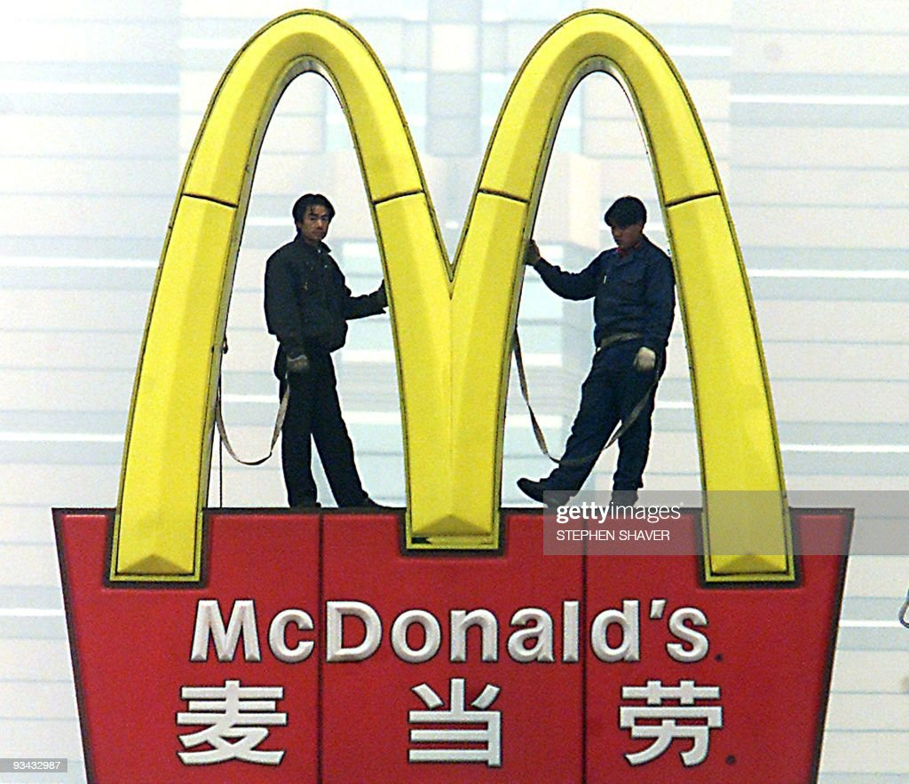 Two Chinese technicians wait for additional fluorescent tubes to be brought up to them as they replace the lights in McDonald's famous yellow arches...