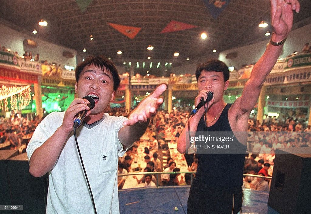 Two Chinese teenagers sing karaoke to a huge international crowd of beer drinkers 12 July at the '98 Qingdao International Beer Festival, China's biggest beer festival, which is being held in the former German concession Qingdao. Last year 1.2 million people attended the festival, consuming more than 496,000 litres of beer from both foreign and local breweries. AFP PHOTO/Stephen SHAVER