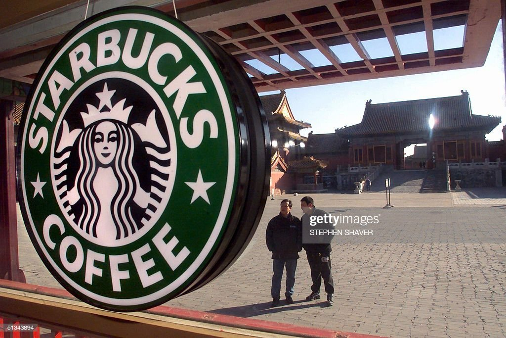 Two Chinese tourists look 10 November 2000 at a Starbucks coffee shop which has opened in the heart of Beijing's historic Forbidden City once the...