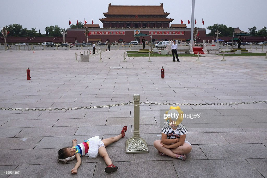 Two Chinese tourists rest in Tiananmen Square on June 4, 2014 in Beijing, China. Twenty-five years ago on June 4, 1989 Chinese troops cracked down on pro-democracy protesters and in the clashes that followed scores were killed and injured.