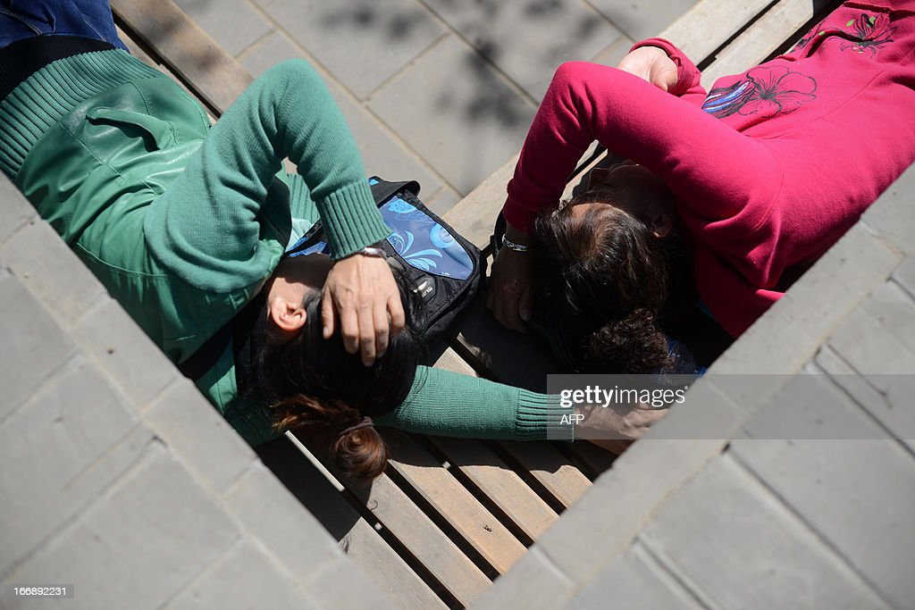 Two Chinese women rest on a bench at a park in Beijing on April 18, 2013. The historic 700 year old park includes a 45 metre man-made hill which was built to provide a favourable Feng Shui environment for the nearby Forbidden City.