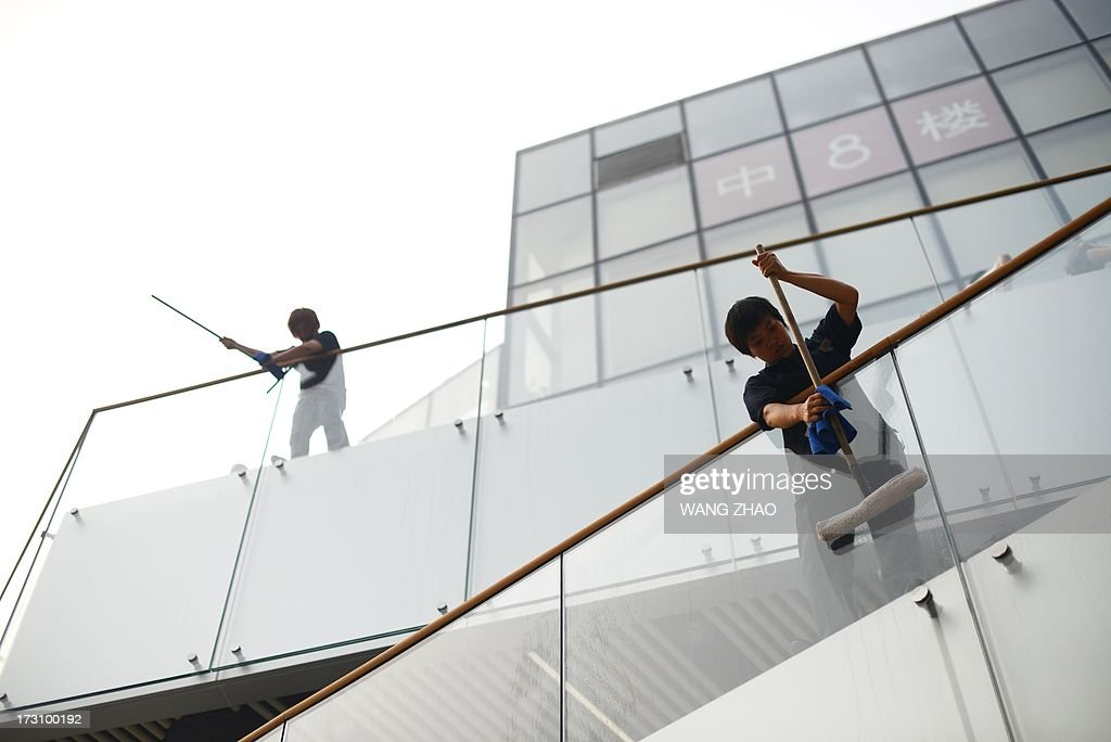Two Chinese workers clean glass panels at a mall in Beijing on July 7,2013. Chinese manufacturing activity contracted further in June, data showed on July 1, with a closely watched survey hitting a nine-month low and adding to signs of weakness in the world's second-largest economy.