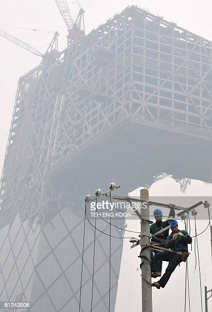 Two Chinese workers install electricity near the ongoing construction of the China Central Television tower through the air pollution at the Central...