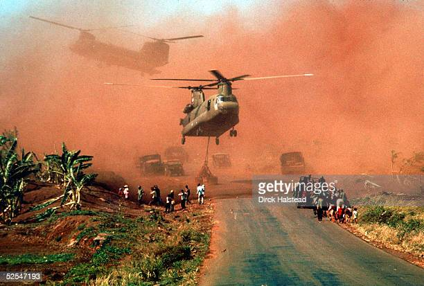 Two Chinook helicopters hover above a road as they assist in evacuating supplies and soldiers of the South Vietnamese 18th Division and their...