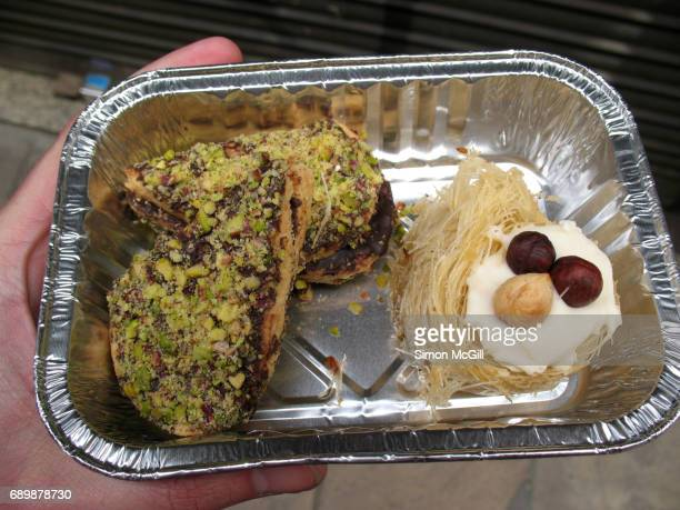 Two chocolate and pistachio nut pastries and an angel hair pastry and hazelnut baklava in an aluminium takout tray held in a young man's hand in a street in Barcelona, Spain