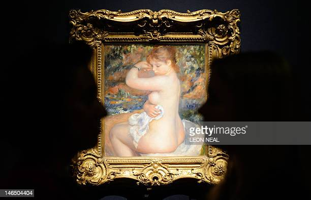 Two Christie's employees pose in front of French artist PierreAuguste Renoir's 'Baigneuse' at a viewing at Christie's auction house in central London...