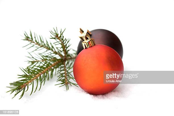 Two christmas baubles with a sprig of fir on snow