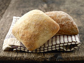 two ciabatta bread buns on wooden table