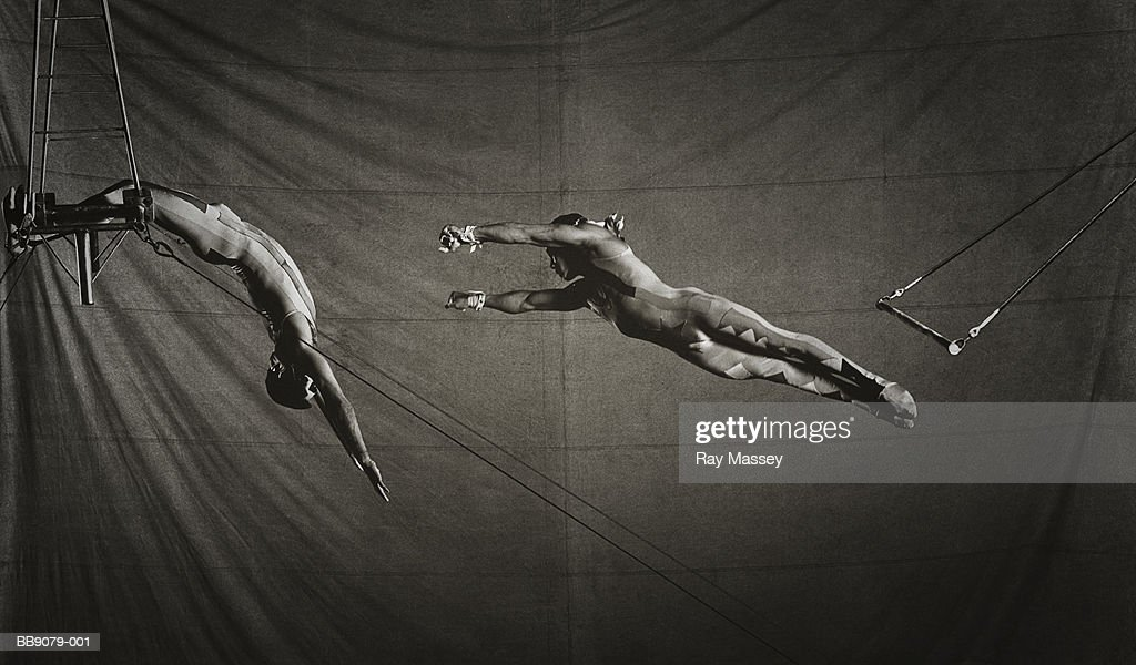 Two circus trapeze artists in action (toned B&W)