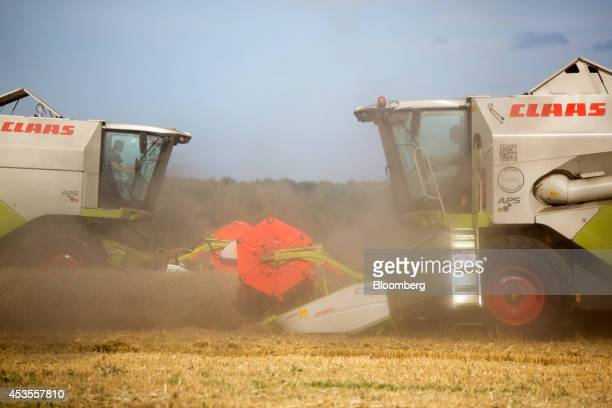 Two Claas KGaA C750 combine harvesters pass while harvesting a wheat field during the summer harvest on the OOO Barmino farm enterprise in Vargany...