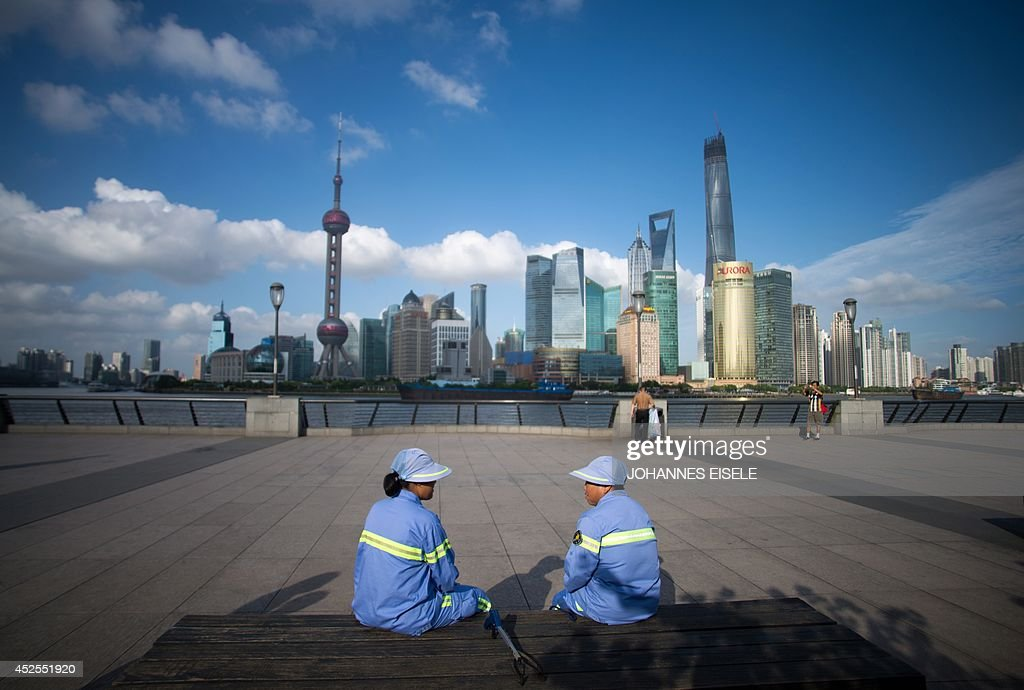 Two cleaners have a rest on a bench at the Bund before the Huangpu River and the skyline of the Lujiazui Financial District in Shanghai on July 23, 2014. Chinese growth accelerated to a forecast-beating 7.5 percent in the second quarter, official data showed on July 16, as government stimulus provided a much-needed boost to the world's second-largest economy.