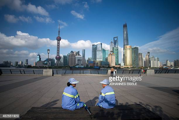 Two cleaners have a rest on a bench at the Bund before the Huangpu River and the skyline of the Lujiazui Financial District in Shanghai on July 23...