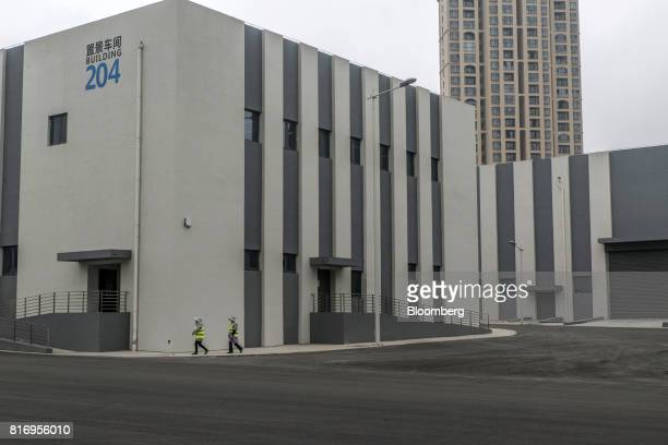 Two cleaners walk past a film studio building inside the Dalian Wanda Group Co Oriental Movie Metropolis project site in Qingdao China on Saturday...