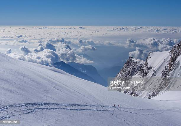 Two climbers above the clouds on Monte Rosa, Alps, Valle dAosta, Italy