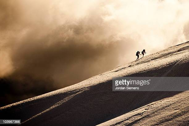 Two climbers hiking in the snow.