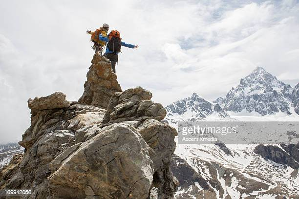 Two climbers stand on rock summit, arms outstretch
