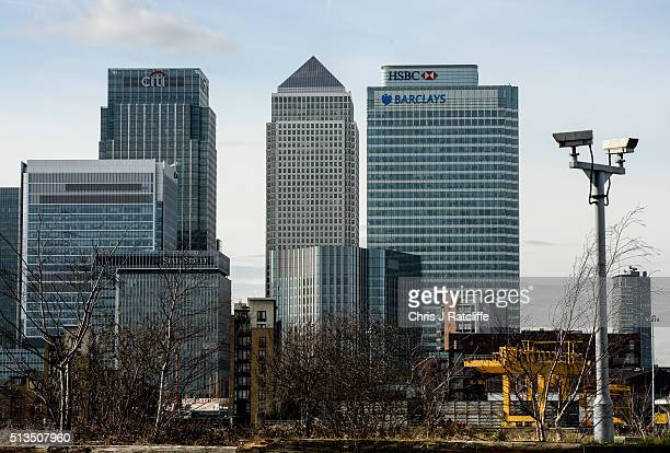 Two closed circuit television cameras on the south bank of the River Thames in the foreground of the financial district Canary Wharf in London The...