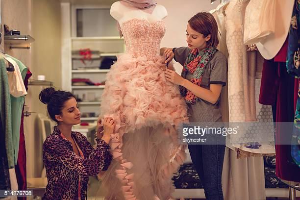 Zwei Mode-Designer arbeiten mit Schaufensterpuppe im Mode-design-studio.