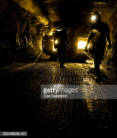Two coal miners in mine shaft (yellow tone) : Stock Photo