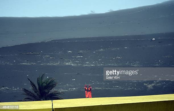 Two coast guards stand guard by the coast near the Wushi harbor in Yilan as typhoon Goni approaches in eastern Taiwan on August 22 2015 Two people...