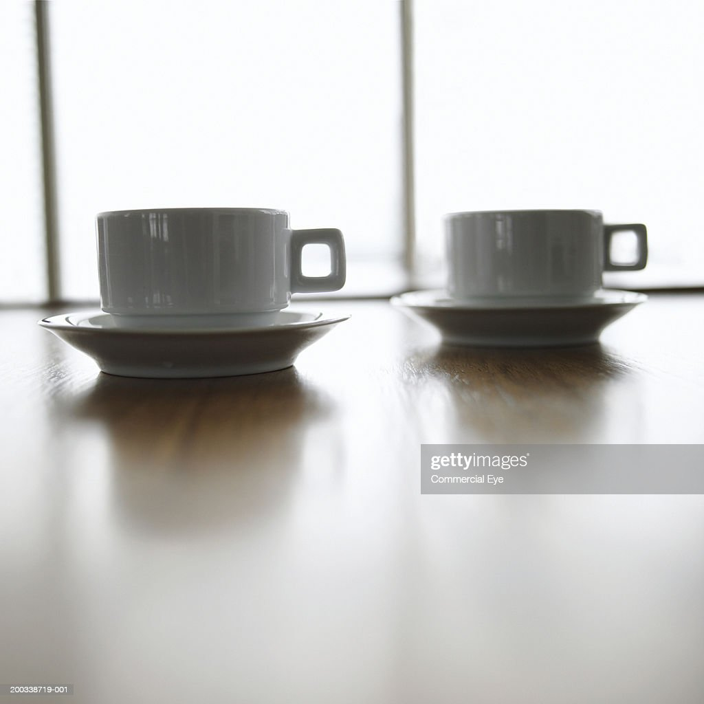 Two coffee cups sitting on table, close-up : Stock Photo