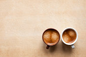 Two coffee espesso cups on brown table. Brown and white espresso cups for coffee lovers. Top view copy space for your design and text