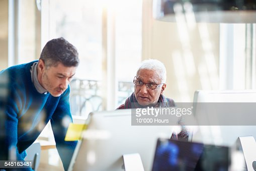 Two colleagues at workstations in modern office