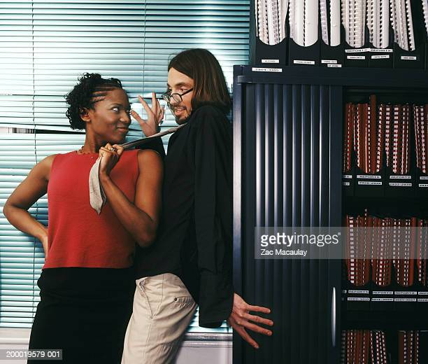 Two colleagues beside filing cabinets, woman pulling man's tie