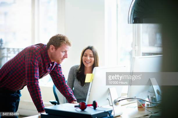 Two colleagues discussing a project on a computer