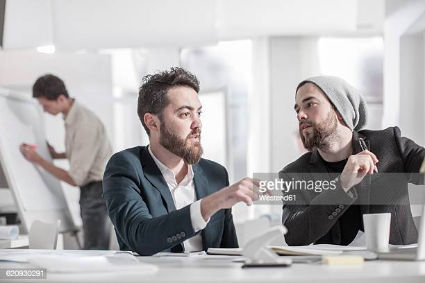 Two colleagues discussing at desk