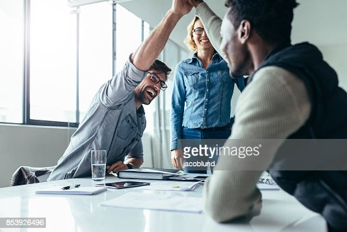 Two colleagues giving high five during meeting : Stock Photo