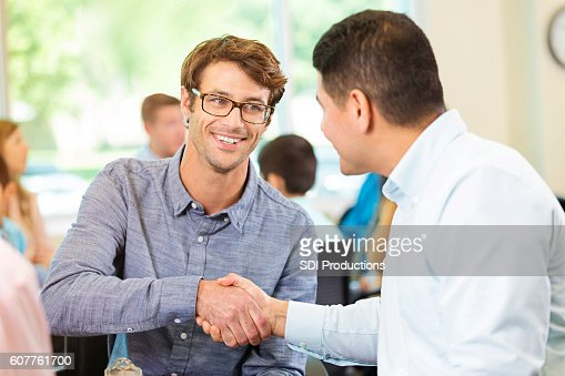 Two colleagues greet one another during meeting