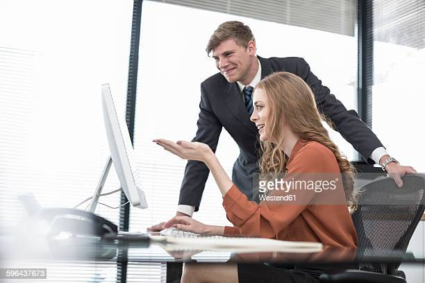 Two colleagues in office looking at computer screen