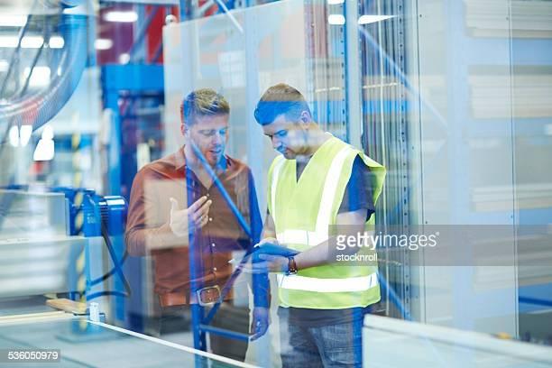 Zwei Kollegen in Fabrik mit digitalen tablet