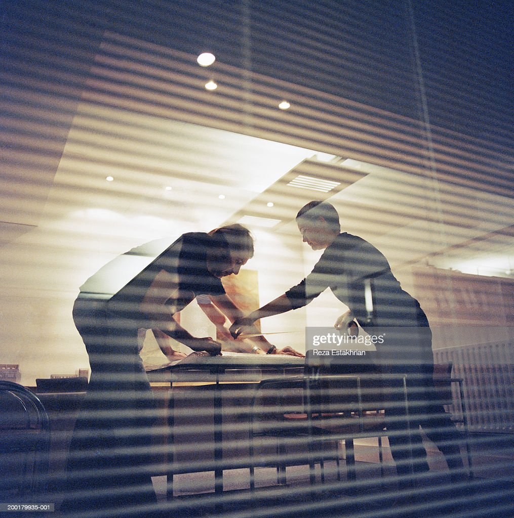 Two colleagues preparing package for mailing in conference room : Stock Photo