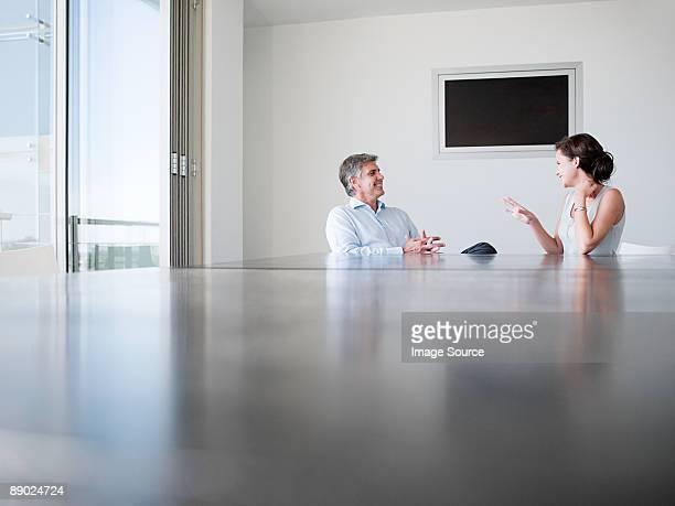 Dos colegas hablando en una sala de conferencias