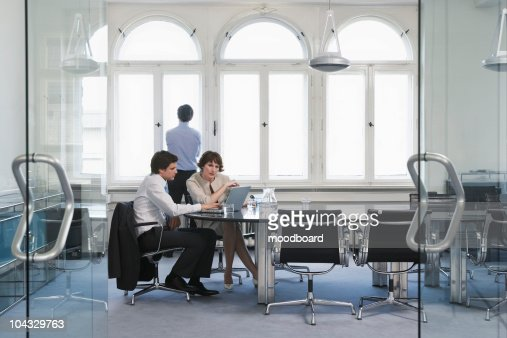 Two colleagues using laptop in office, another looking out window : Stock Photo