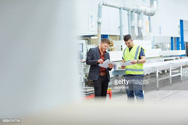 Two colleagues with documents on factory shopfloor