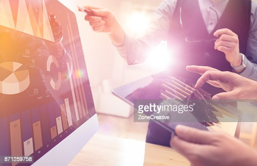 Two colleagues working on new global financial strategy plan using tablet and laptop.Modern business team innovation concept.Project meeting at office with virtual graph and chart data interface : Stock Photo
