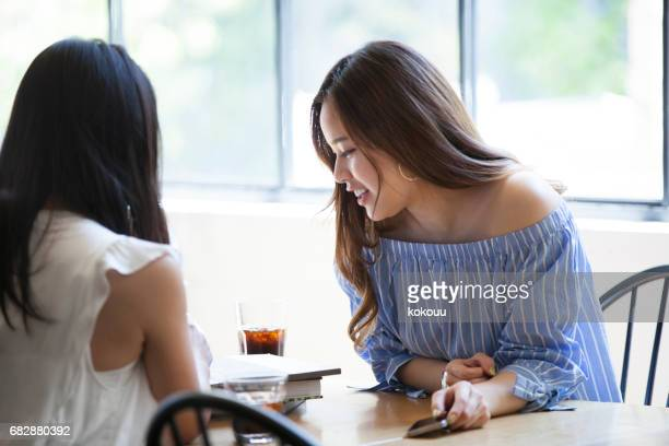 Two college girls spend a quiet morning at a cafe.