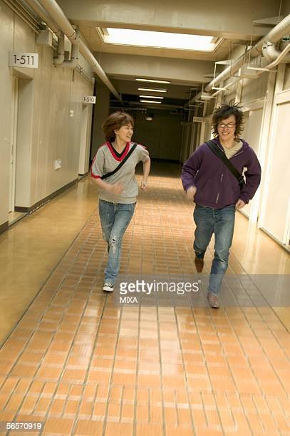 Two college students running down corridor
