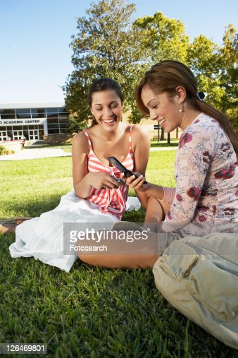 Two college students using cell phones in park
