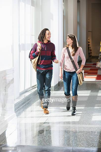 Two college students walking down hallway