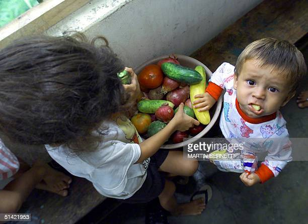 Two Colombian refugee children hold vegetables in the kitchen 08 December 2000 in Lago Agrio Ecuador Dos ninos colombianos toman frutas en la cocina...