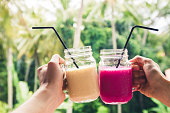Two colorful fruit shakes in hands. Summer and tropical mood. Cold blended drinks, banana and dragon fruit smoothie. Clink glasses by couple hands