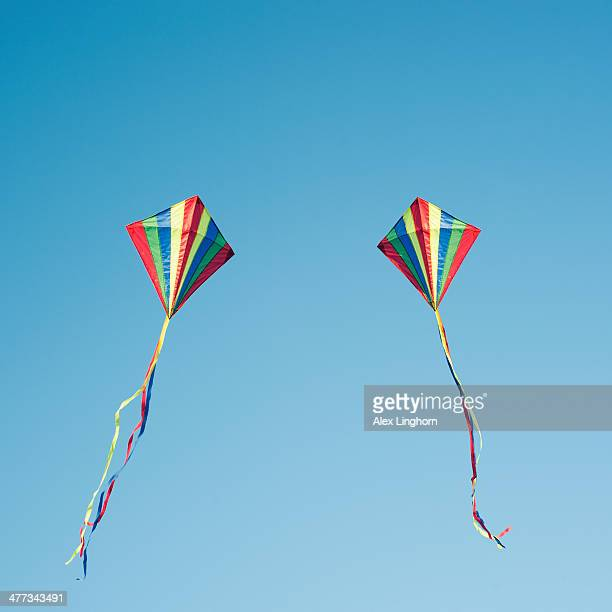 Two colourful kites flying in blue sky