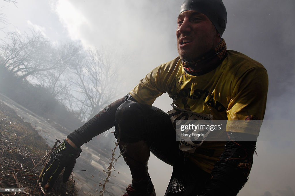 Two competitor heaves himself out of a water obstacle during the Tough Guy Challenge on January 27, 2013 in Telford, England.