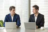Two confident businessmen sitting at office desk with laptops, looking at each other with hate dislike, rivals accepting challenge, business competition, team rivalry at work, competitors behavior