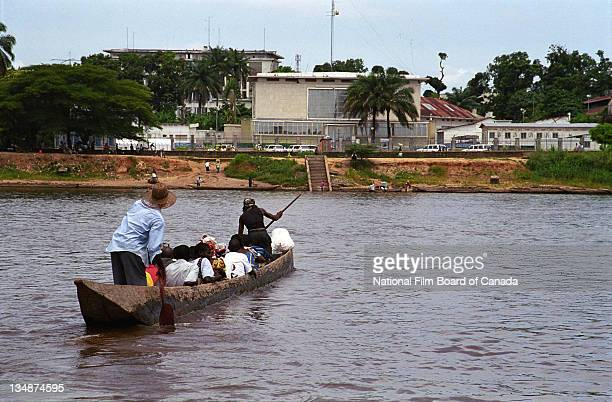 Two Congolese men steer their wooden dugout canoe crowded with people towards the shore near Kisangani Democratic Republic of the Congo 2003 Photo...