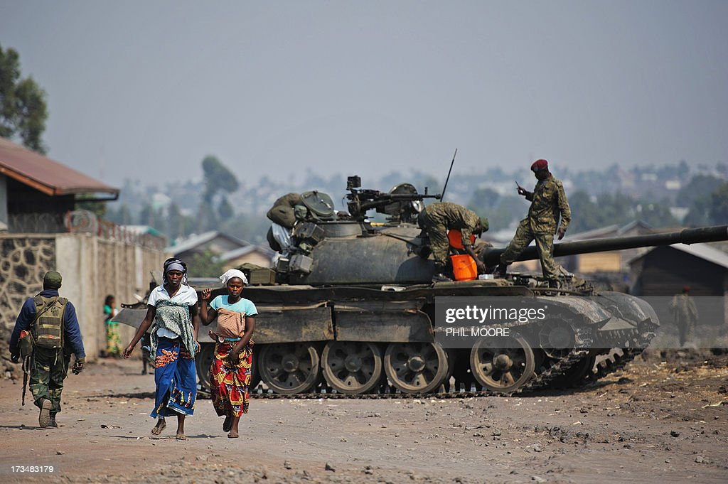 Two Congolese women walk past a government army tank in Munigi on the outskirts of Goma in the east of the Democratic Republic of the Congo on July...